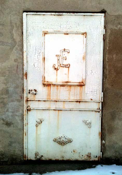 Initiales poinçonnées sur porte en métal d'une cave